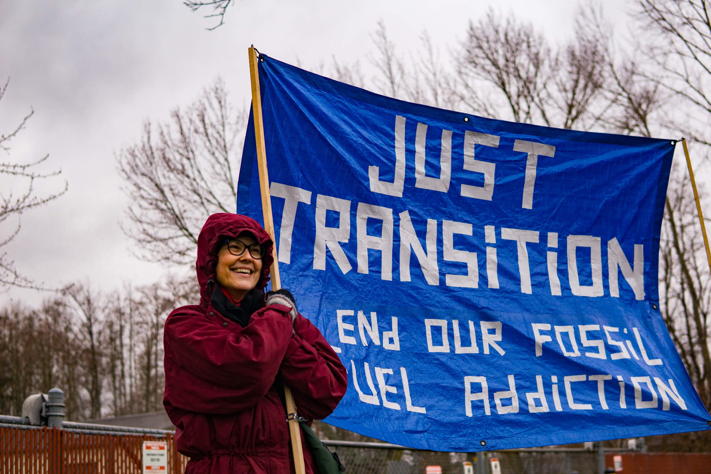 """A person in a red coat smiling holds up a blue tarp with written words: """"Just Transition, end our fossil fuel addiction"""""""